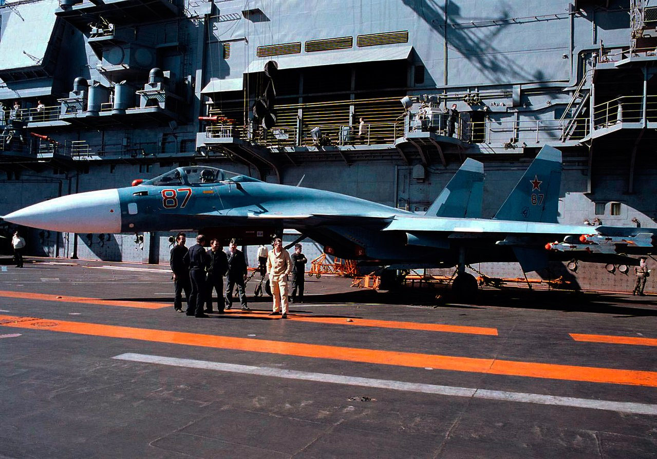 A Su-33 onboard Admiral Kuznetsov in 1996. U.S. Navy sailors from USS San Jacinto are visiting the c